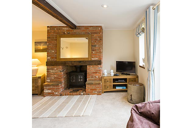 Oyster Cottage's lounge fireplace with wood burner