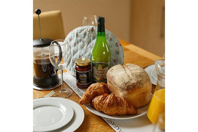 Lapwing Cottage's kitchen table set with coffee, bread, croissants…