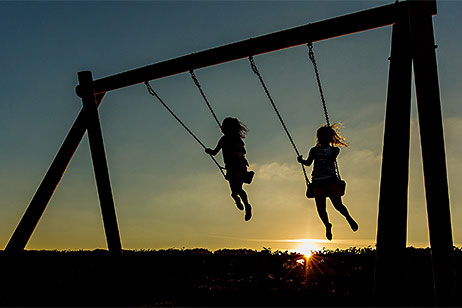 Two young children on the swings with the sun setting behind